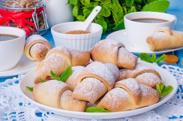 Mini croissants com damascos secos, figos e nozes em um prato com uma xícara de café