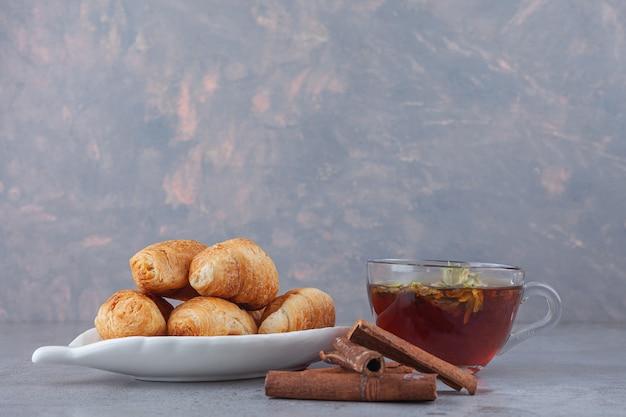 Mini croissants de massa folhada com crosta dourada e uma xícara de chá.