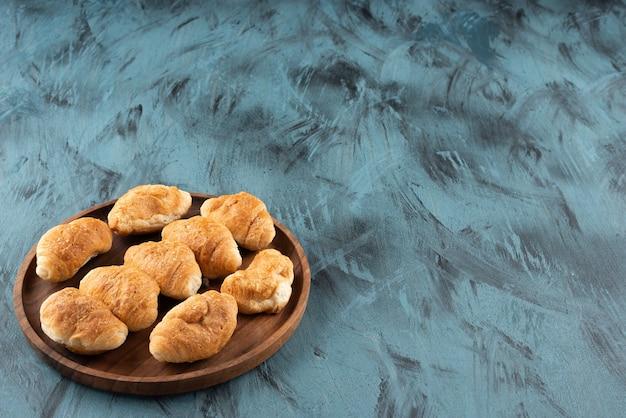 Mini croissants doces em uma placa de madeira sobre um fundo azul escuro.