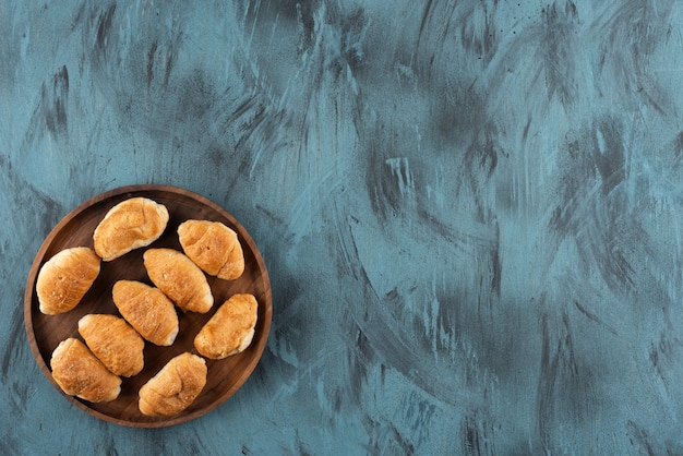 Mini croissants doces em uma placa de madeira sobre uma superfície azul escura