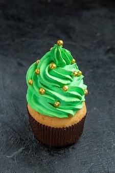 Mini cupcake da árvore de natal no escuro com vista frontal