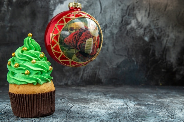 Mini cupcakes coloridos bola de árvore de natal vermelha em lugar escuro de vista frontal foto de natal