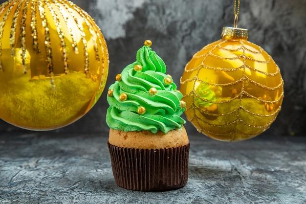 Mini cupcakes coloridos brinquedos de bola de árvore de natal amarela em fundo escuro de vista frontal