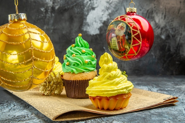Mini cupcakes coloridos de frente, bolas de árvore de natal vermelhas em jornal em foto de ano novo escuro
