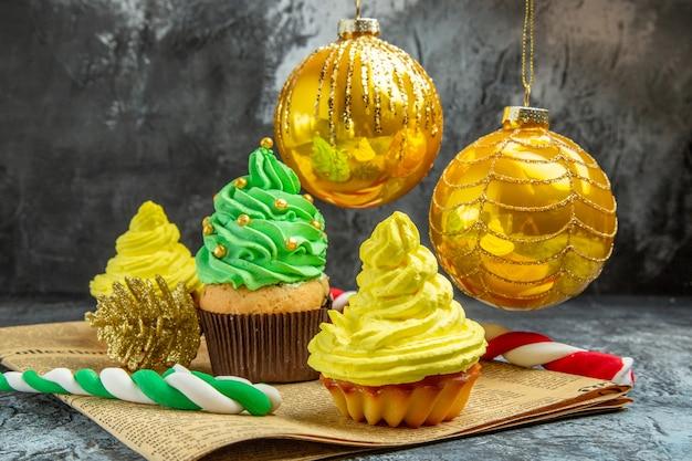 Mini cupcakes coloridos de frente, brinquedos para árvores de natal e doces no jornal na foto de ano novo escuro