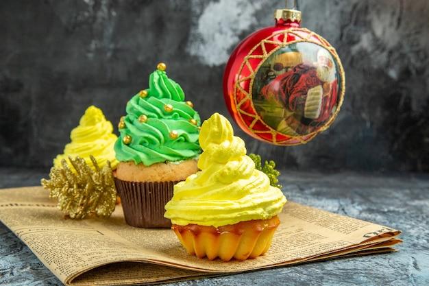 Mini cupcakes coloridos de frente, brinquedos para árvores de natal vermelhas no jornal na foto de ano novo escuro