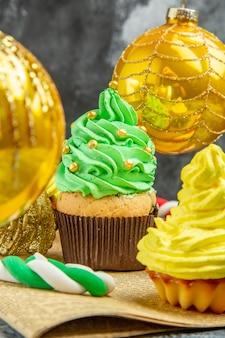 Mini cupcakes coloridos de frente para a árvore de natal brinquedos doces de natal no jornal na foto de ano novo escuro
