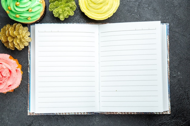 Mini cupcakes coloridos de vista de cima de perto e um caderno em fundo escuro