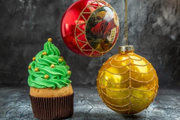 Mini cupcakes coloridos de vista frontal, bolas de árvore de natal vermelhas e amarelas na foto escura de natal