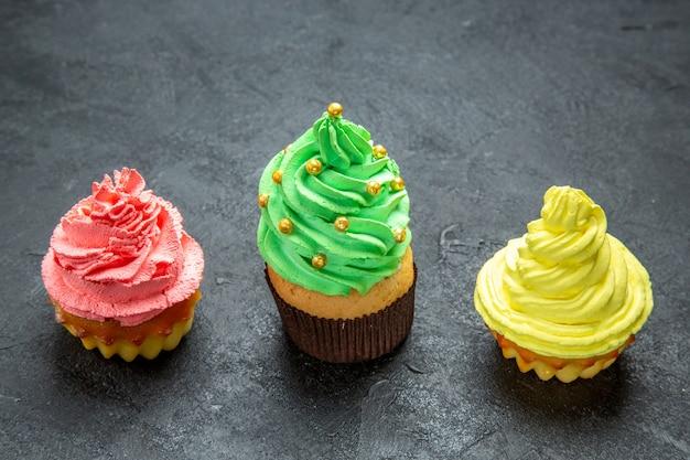 Mini cupcakes coloridos em linha horizontal de vista frontal em um espaço livre de fotos de natal escuro