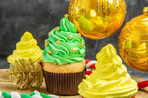 Mini cupcakes coloridos pendurados na árvore de natal, brinquedos e doces de natal no jornal na foto do ano novo.
