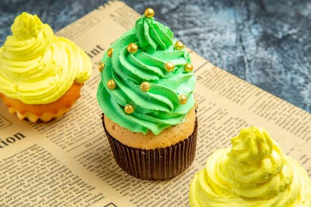 Mini cupcakes de frente no jornal no escuro