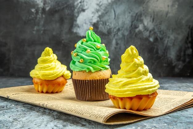 Mini cupcakes de vista frontal no jornal na foto escura do natal