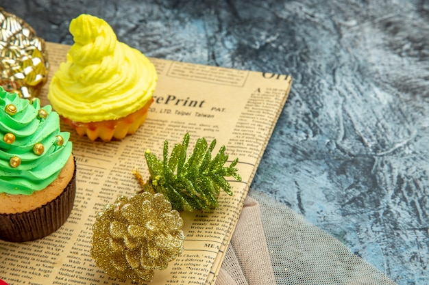 Mini cupcakes enfeites de natal no jornal xale bege em fundo escuro, lugar livre com vista inferior