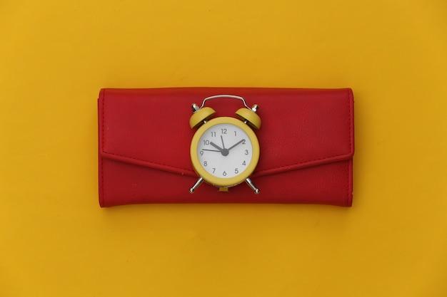 Mini despertador e carteira vermelha em fundo amarelo.
