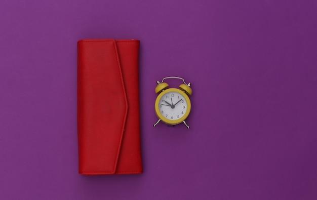 Mini despertador e carteira vermelha em fundo roxo.