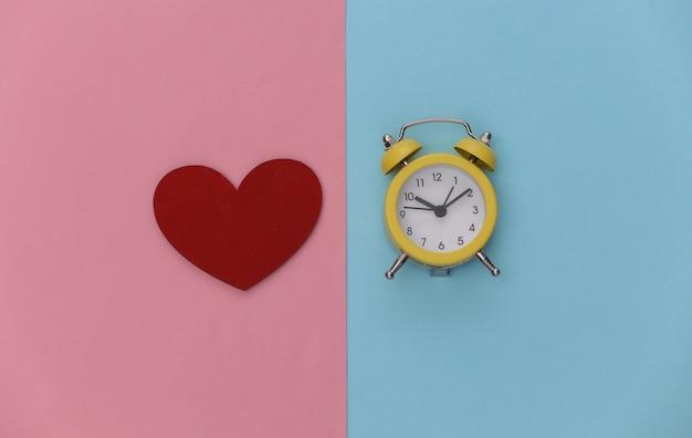 Mini despertador e coração vermelho em fundo rosa azul pastel.