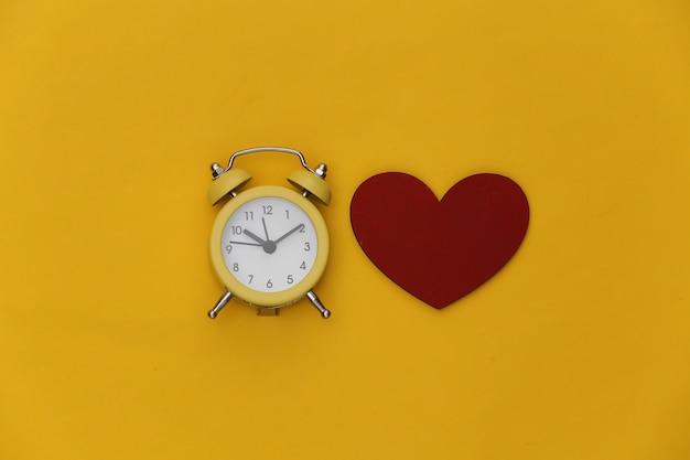 Mini despertador e coração vermelho sobre fundo amarelo.
