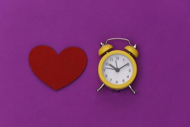 Mini despertador e coração vermelho sobre um fundo roxo.