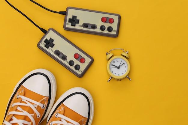 Mini despertador e joysticks retrô, tênis em fundo amarelo.