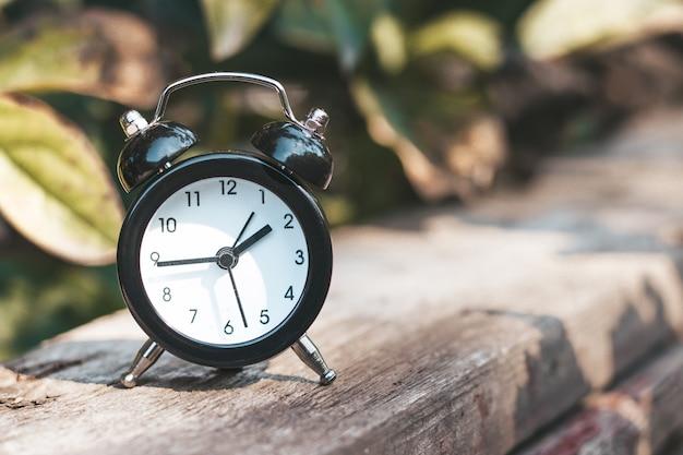 Mini despertador preto na superfície de madeira na natureza, folhagem verde no fundo. conceito de tempo. imagem abstrata.