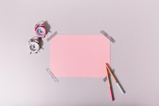 Mini-despertadores ao lado do conjunto de papelaria rosa