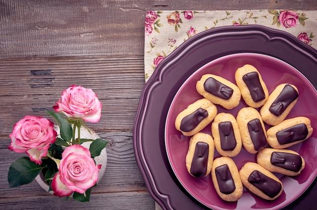 Mini éclairs de baunilha com cobertura de chocolate no prato roxo, vista superior na mesa de madeira rústica