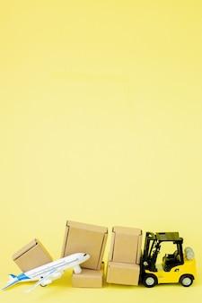 Mini empilhadeira carrega caixas de papelão no avião. entrega rápida de mercadorias e produtos.