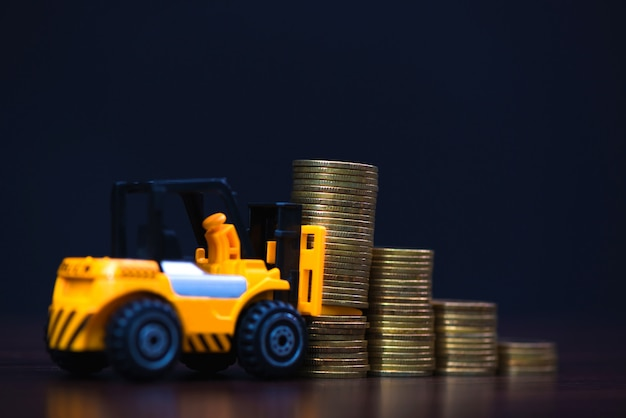 Mini empilhadeira carregando moeda de pilha com etapas de moeda de ouro no escuro