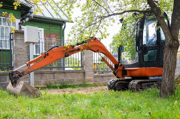Mini escavadeira na cor laranja. aluguel de equipamentos de construção.