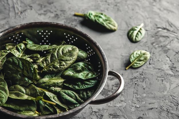 Mini espinafre fresco em uma peneira na velha mesa de concreto. alimentação saudável, produto ecológico. vegan