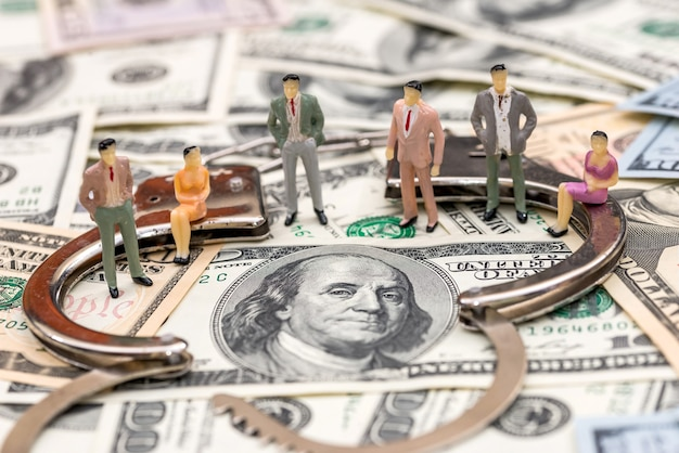 Mini figuras perto de algemas de aço em fundo de notas de dólar