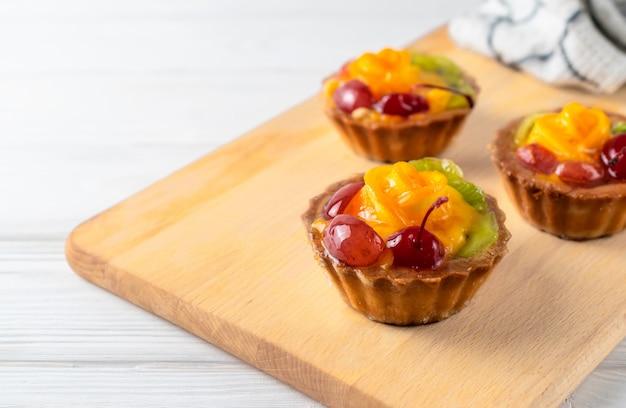 Mini galdérias misturadas da fruta com cereja e quivi alaranjados na placa de madeira.