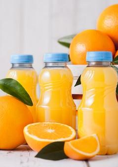 Mini garrafas plásticas de suco de laranja orgânico fresco com laranjas cruas em caixa de madeira branca