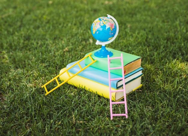 Mini globo em cima da pilha de livros didáticos