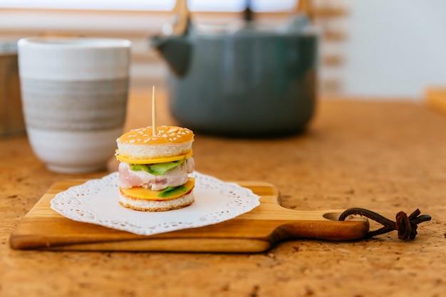 Mini hamburguer da galinha na placa de desbastamento de madeira com o copo e a caneca de chá do borrão no fundo.