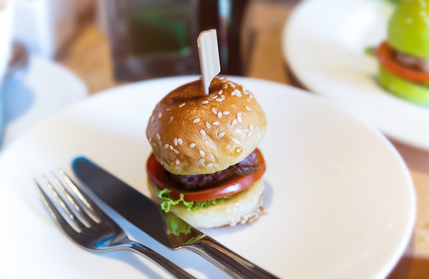 Mini hambúrguer definido em chapa branca.