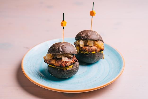 Mini hambúrguer gourmet de carne com pão preto no prato