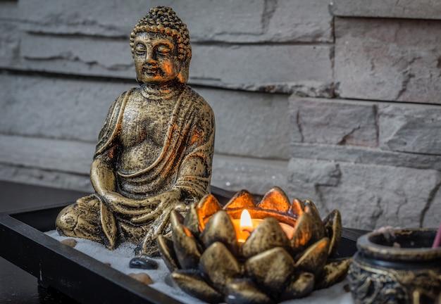 Mini, jardim zen de mesa com vela acesa e pequeno buda nele.