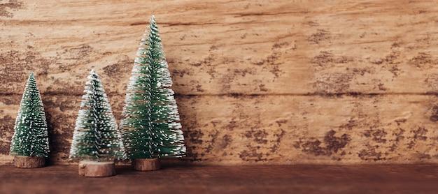 Mini madeira de árvore de natal na mesa de madeira rústica e parede de madeira