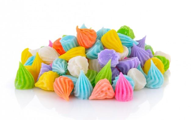 Mini merengues coloridos na parede branca