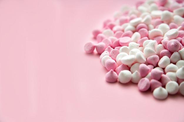 Mini merengues rosa e branco em forma de gotas, que se encontram em um fundo rosa com copyspace