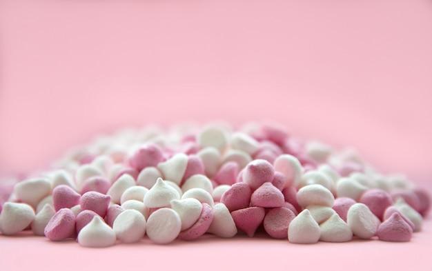 Mini merengues rosa e branco em forma de gotas, que se encontram em uma superfície rosa.