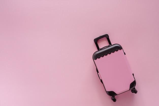 Mini modelo de brinquedo pinky bagagem no fundo colorido pastel pinky para viajar