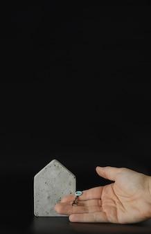 Mini modelo de casa de concreto e mão com chave no fundo preto. compre uma casa. conceito de escada de propriedade, hipoteca e investimento imobiliário. espaço livre para texto, cópia espaço, layout moderno.