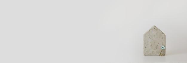 Mini modelo de casa de concreto e uma chave no fundo branco. compre uma casa. conceito de escada de propriedade, hipoteca e investimento imobiliário. espaço livre para texto, cópia espaço, layout moderno.