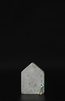 Mini modelo de casa de concreto e uma chave no fundo preto. compre uma casa. conceito de escada de propriedade, hipoteca e investimento imobiliário. espaço livre para texto, cópia espaço, layout moderno.