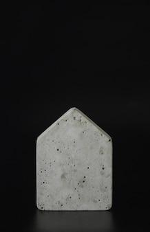 Mini modelo de casa de concreto no fundo preto. compre uma casa. conceito de escada de propriedade, hipoteca e investimento imobiliário. espaço livre para texto, cópia espaço, layout moderno.