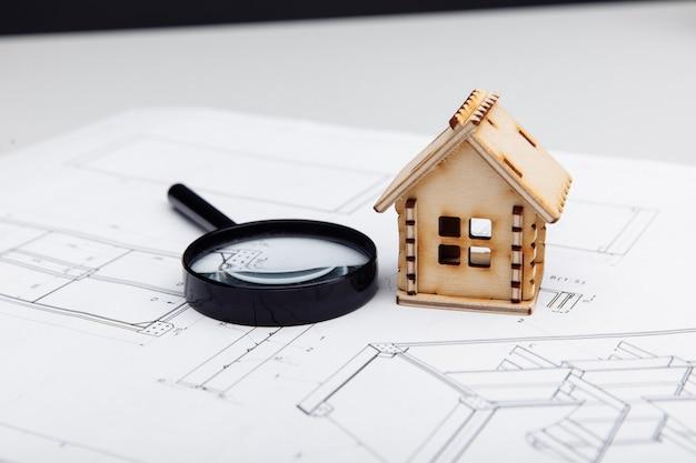 Mini modelo de casa e lupa sobre um conceito de construção imobiliária em desenho