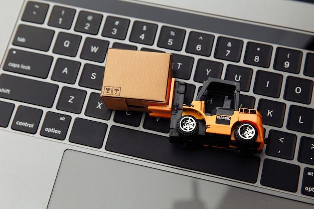 Mini modelo de empilhadeira com caixa de papelão no laptop. logística e conceito de entrega.